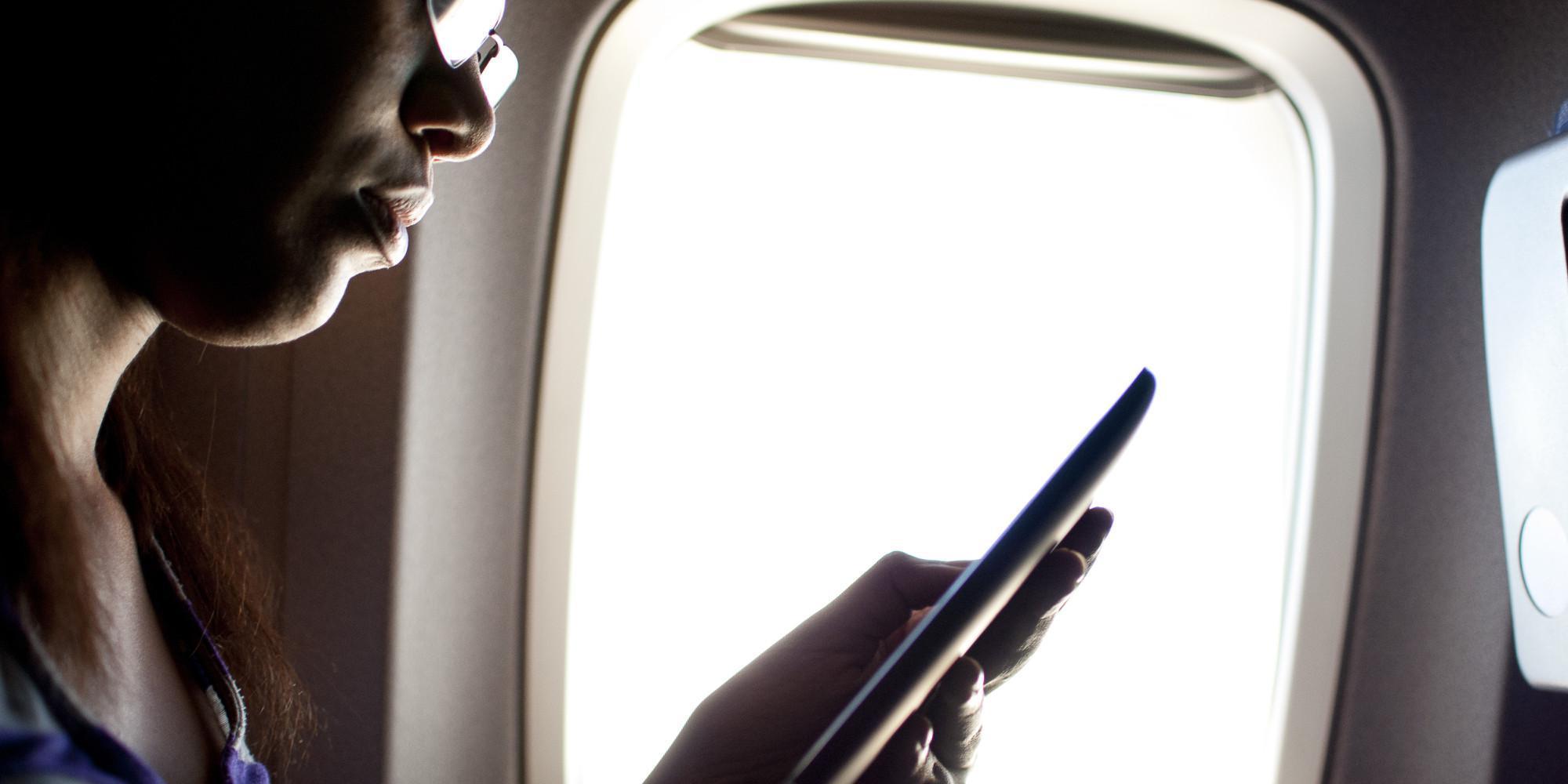 A woman using an ereader on a plane